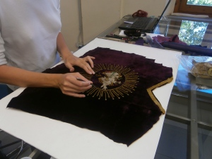 mani al restauro su tessuti antichi